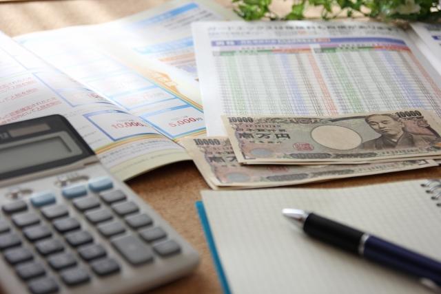 保険のパンフレットと現金と計算機