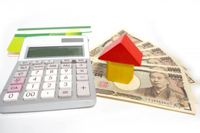 不動産取得税の計算に使う電卓と家の積み木と現金
