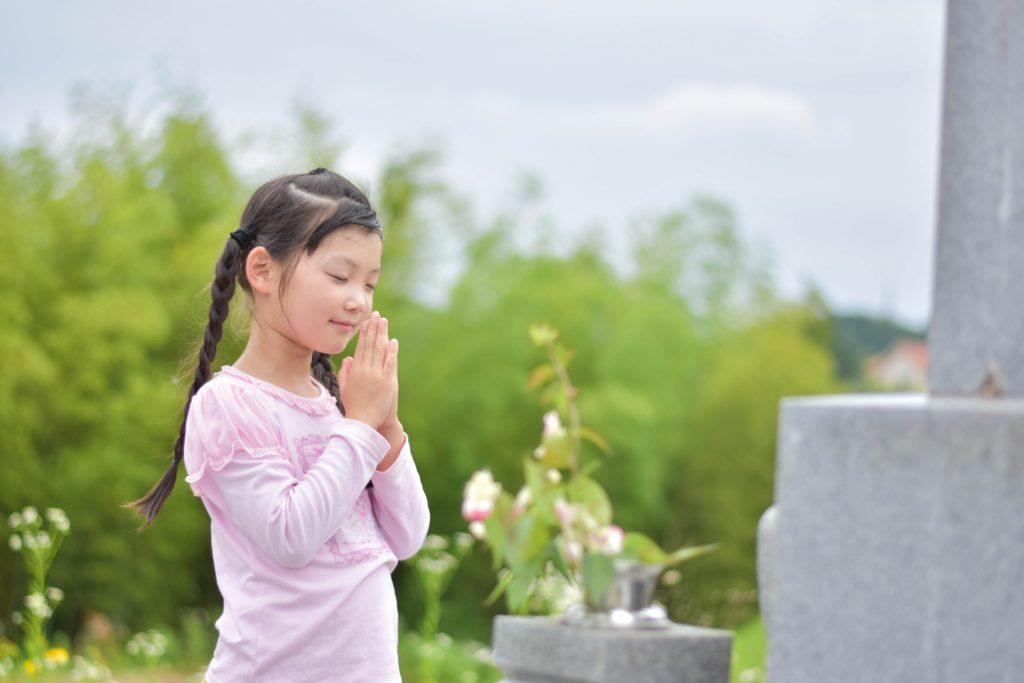 墓の前で手をあわせる女の子