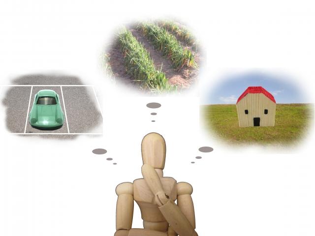 土地や家や車といった財産のことを考える人形