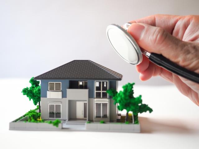 不動産の調査を表す一戸建ての模型と聴診器