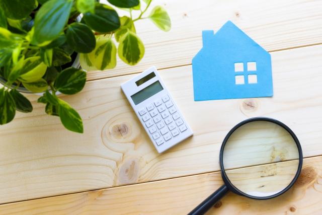 相続財産の調査を意味する不動産と電卓と虫眼鏡