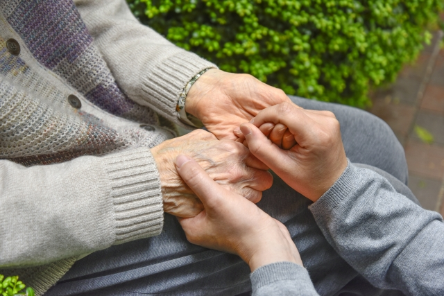認知症の心配を抱える老人の手を握る女性の手
