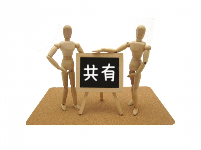 共有と書かれた看板前に立つ2つの人形