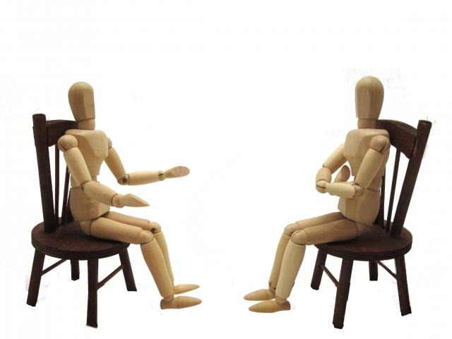 イスに座って遺留分の話合いをする人形