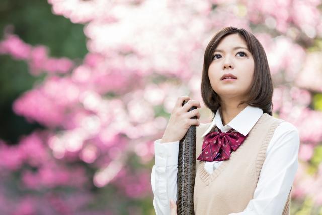 桜の前で卒業証書をもつ女学生