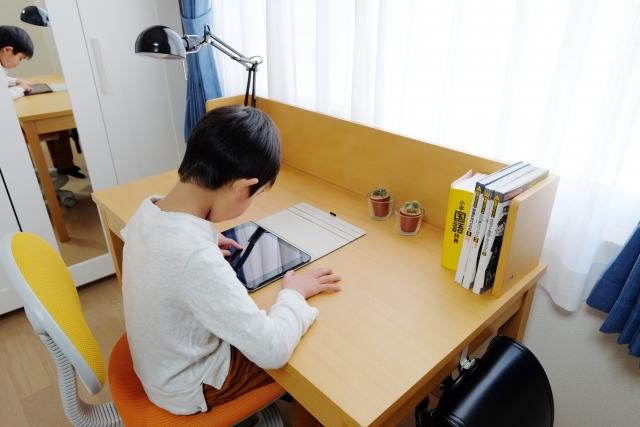 机に向かって勉強をする子供
